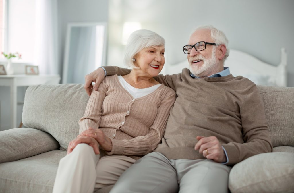 Happy senior couple in independent living community sitting together on couch